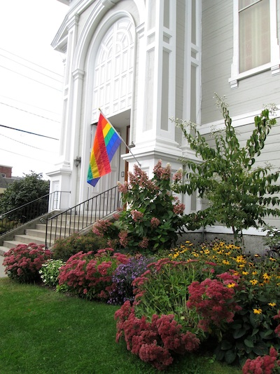 Exterior of church with rainbow flag.