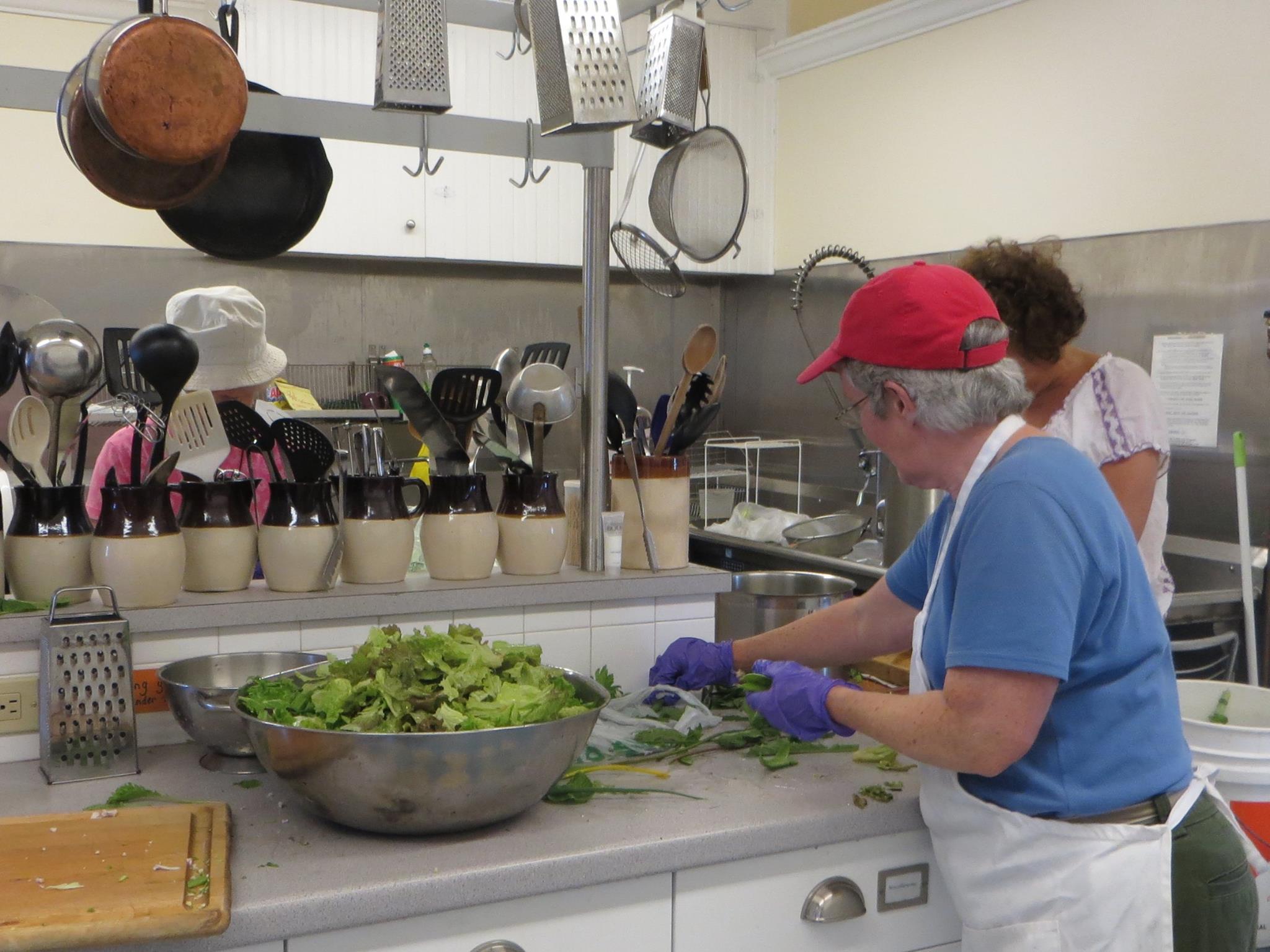 Volunteers in kitchen prepare salad greens for community lunch.