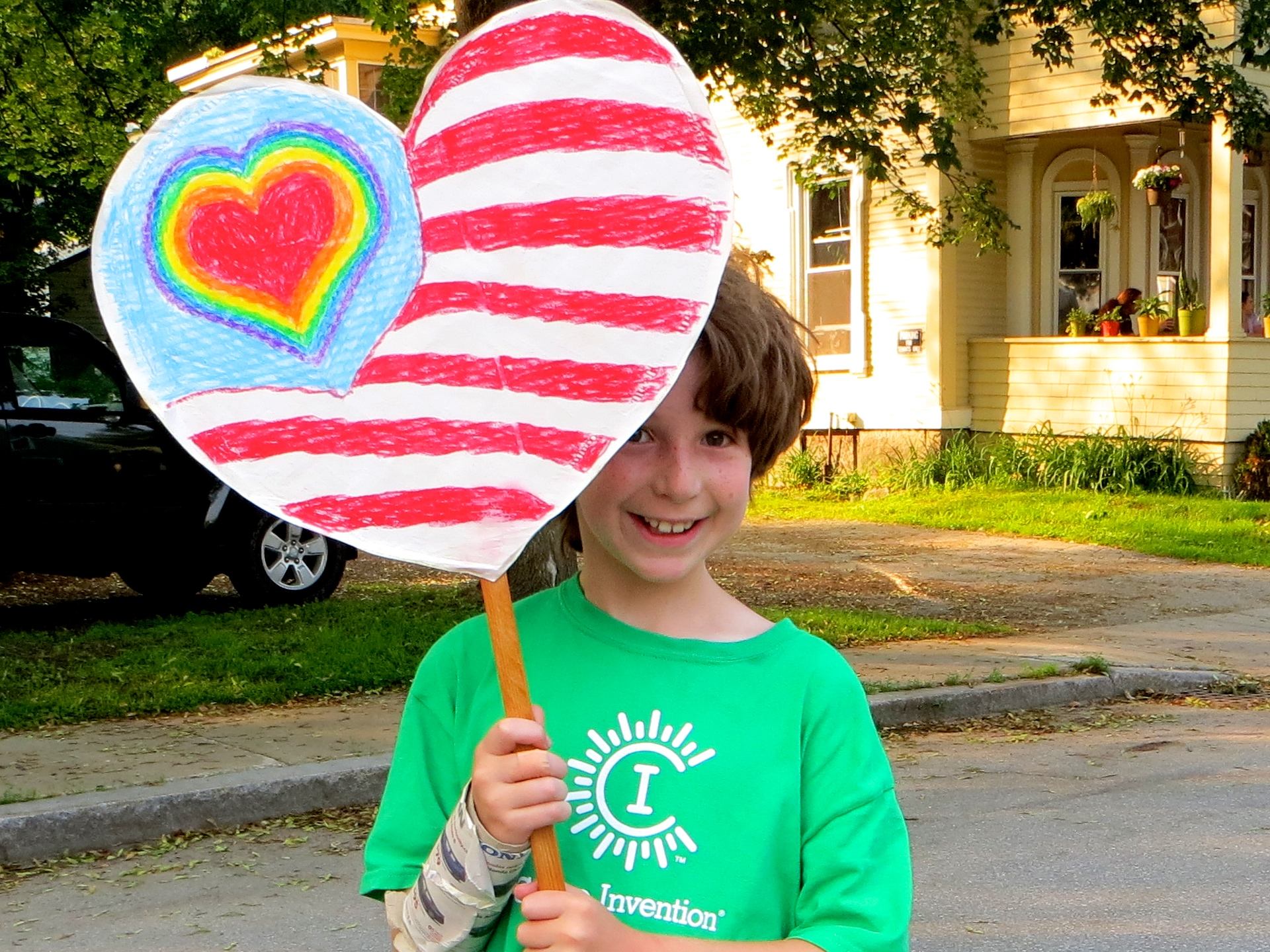 Boy holding hand colored heart shaped banner.