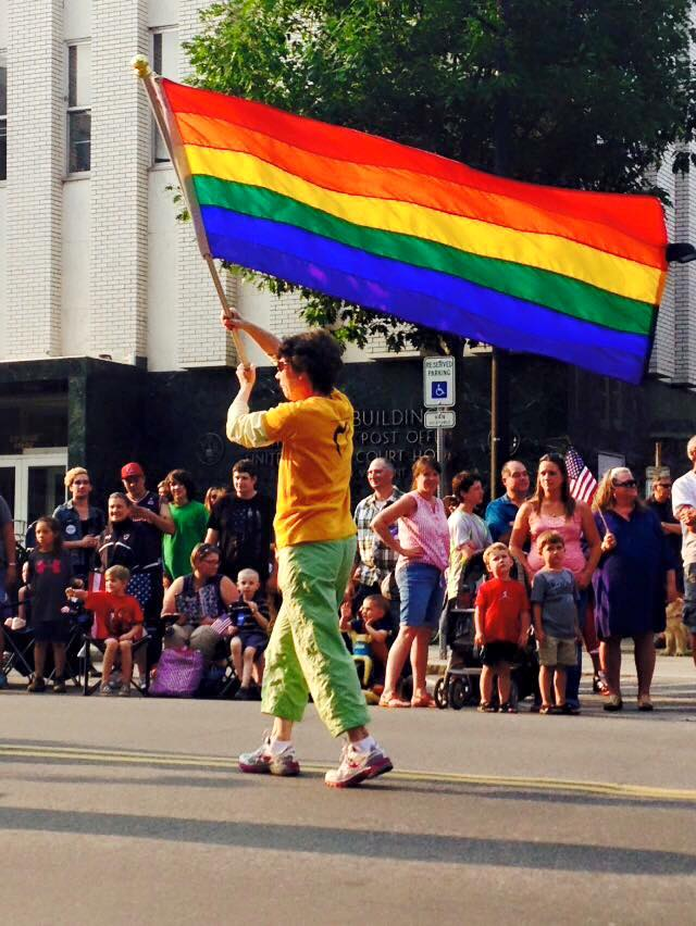 UCM member carries rainbow flag.