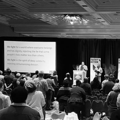 Black and white photo of people gathered in conference room with two speakers up front and words projected on screen